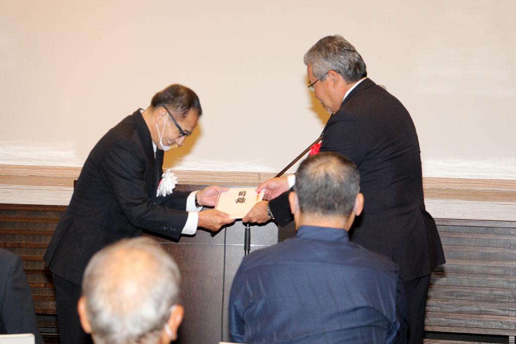 與那覇 博明実行委員会副会長から上原 源三学校長へ目録の贈呈