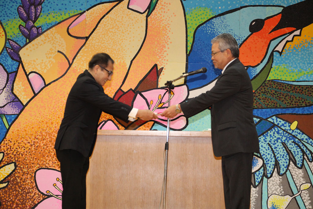 與那覇副会長から上原校長先生へ創立百十周年記念事業寄附金1千43万円を贈呈する